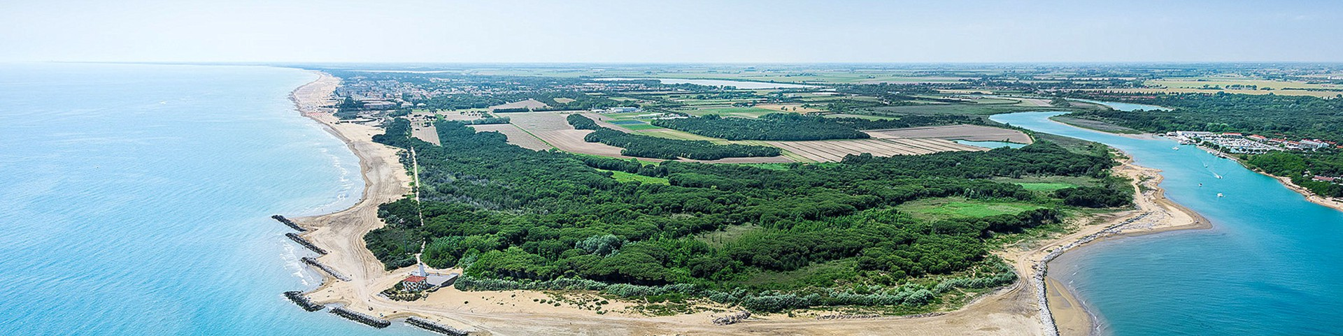 V popředí přírodní rezervace a řeka Tagliamento, vlevo v dáli část Bibione Lido dei Pini